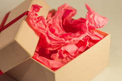 Light-coloured box with pink present paper. Light-coloured opened square present box without lid with pink paper inside on the light background stock photos