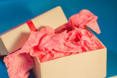 Light-coloured box with pink present paper. Light-coloured opened square present box without lid with pink paper inside on the blue background stock photography
