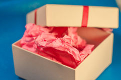 Light-coloured box with pink present paper. Light-coloured opened square present box without lid with pink paper inside on the blue background stock image