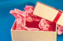 Light-coloured box with pink present paper. Light-coloured opened square present box without lid with pink paper inside on the blue background royalty free stock photo