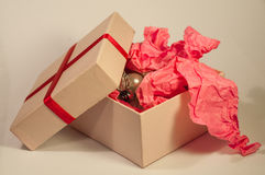 Light-coloured box with pink present paper. Light-coloured opened square present box without lid with pink paper and jewellery inside on the light background royalty free stock photos