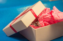 Light-coloured box with pink present paper Stock Photo