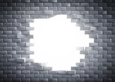 Light coming through a hole in a brick wal Stock Images