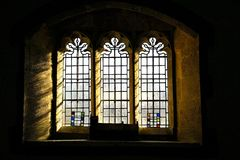 Light coming through old window. Light coming through medieval church  glass stained window, UK Stock Photo