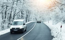 Light commercial vehicle on road in winter. Light commercial vehicle on road in forest in winter stock photo