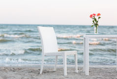 A light composition with white wooden table and chair on the sea or ocean. Blurred background. Stock Photo