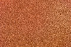 Copper Glitter Background. Light copper colored sand paper textured background with sparkles and glitters stock images