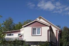 Light cottage on background blue sky. Light cottage in green branch on background blue sky Royalty Free Stock Images