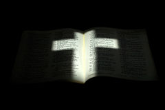 Light Cross on Darkened Bible Royalty Free Stock Photo