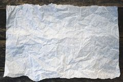 Light crumpled paper. On a wooden background closeup royalty free stock image