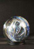 Light within a crystal ball ag. Ainst a dark background Royalty Free Stock Photo