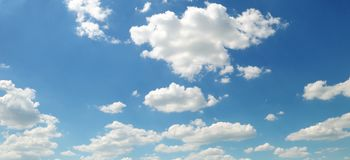Light cumulus clouds against the blue sky. Wide photo. Light cumulus clouds against the blue sky. A bright sunny day. Wide photo Stock Photo