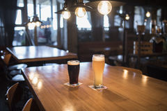 Light and dark beer in glasses on a wooden table in a bar. Light and dark beer in glasses on a table in a bar Royalty Free Stock Photography