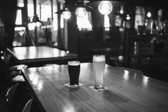 Light and dark beer in glasses on a wooden table in a bar, black and white frame. Light and dark beer in glasses on a wooden table in a bar Stock Photos