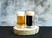 Light and dark beer in mugs on wooden board Royalty Free Stock Images