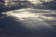 Light in the dark clouds. Dramatic clouds and sunlight shining through stock photography