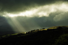 Light on a Dark Day. Crepuscular sunrays burst through dark clouds over a Welsh mountain in Porth, Rhondda, Wales Stock Photos