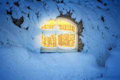 Light decoration in the window in a cold, snowy winter night Stock Photo