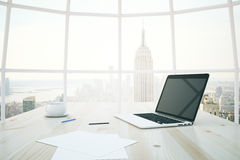 Light desk with laptop. Closeup of light wooden desktop with blank notebook, coffee cup and paper sheets with window and New York city view in the background Stock Photography