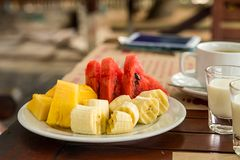 Light dessert fruit plate sliced pieces of fruit watermelon pineapple banana compliment after dinner stock image