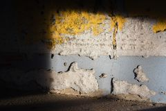 Light disclosed a rundown wall. In yellow and gray Royalty Free Stock Photo