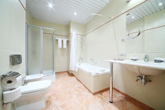 Light and empty bathroom with white bath, toilet Stock Image