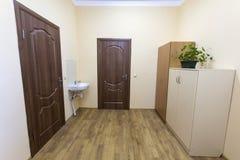 Light empty corridor hall with wooden floor, brown doors and sink. School, office or clinic interior.  stock images