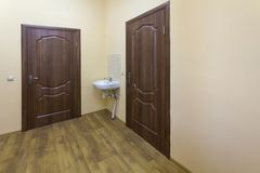 Light empty corridor hall with wooden floor, brown doors and sink. School, office or clinic interior.  royalty free stock photography