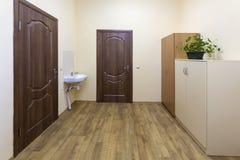 Light empty corridor hall with wooden floor, brown doors and sink. School, office or clinic interior.  stock image