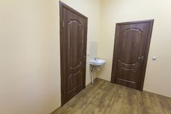 Light empty corridor hall with wooden floor, brown doors and sink. School, office or clinic interior.  royalty free stock photos