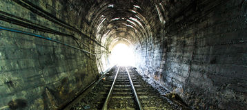 Light at the end of railroad tunnel Stock Photos
