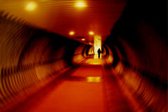Light at the End of the Tunnel. Long tunnel with dramatic lighting and person's silhouette.  Radial blur effect applied Royalty Free Stock Photos
