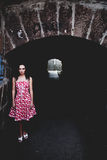 The light at the end of the tunnel. Beautiful slender girl in a red dress against a dark underpass. The light at the end of the tunnel Royalty Free Stock Photography