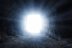 A light in the end of a tunnel. Blue glow at the exit of the dark cave Stock Image