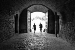 Light at the End of the Tunnel. A couple walking through an arch into the brightness Royalty Free Stock Photos