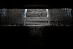 Light at the End of a Tunnel. Lit stairs at the end of a tunnel under a highway. The walls are filled with tiles that reflect the light stock photos
