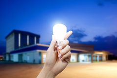 Light energy for industry, Hand holding light bulb in industrial topic Royalty Free Stock Photos