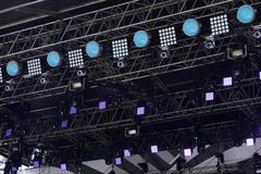 Light equipment with illuminated spot and LED lights installed on metal frame construction. Closeup of concert or show stage