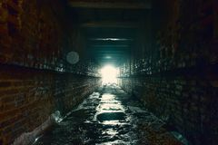 Light and exit in end of dark long brick abandoned industrial tunnel or corridor or sewer channel, way to freedom concept stock photos