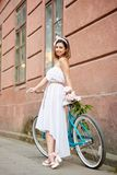 Light female is leaning on retro bicycle with bouquet peonies royalty free stock photography