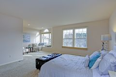 Light filled Master bedroom with lots of space. Light filled Master bedroom boasts black leather tufted bench at the foot of the bed and a cozy reading nook with stock photography