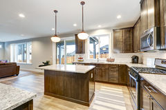 Light filled Northwest kitchen design with kitchen island. Natural brown cabinets topped with granite countertops and paired with white backsplash. Northwest Stock Photo