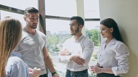 Light-flooded room of four young people two young women and two men smiling laughing and talking to each other tell each stock footage
