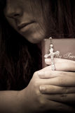 The Light In Forgiving. A female in prayer with her prayer book and cross Royalty Free Stock Photos