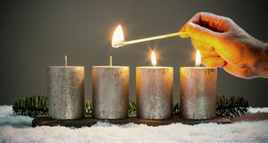 Light four advents candles with matches Stock Photography