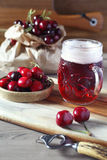 Light fruit craft beer and cherry. On wooden chopping board, rustic style stock photo