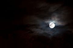 Light of a full moon. A full moon shines through the clouds Royalty Free Stock Photography