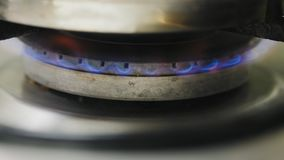 Light gas stove with match. A man lighting the gas-stove with a match, close-up shot stock video