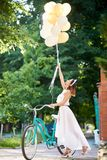 Light girl near retro bicycle holds up raised helium balloons. A light girl near a retro bicycle holds up the raised helium balloons in the sun`s rays. Concept Royalty Free Stock Images