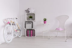 So light, so girly  and so beautiful!. White bike, DIY bookcase and white chair in spacious interior Royalty Free Stock Photos